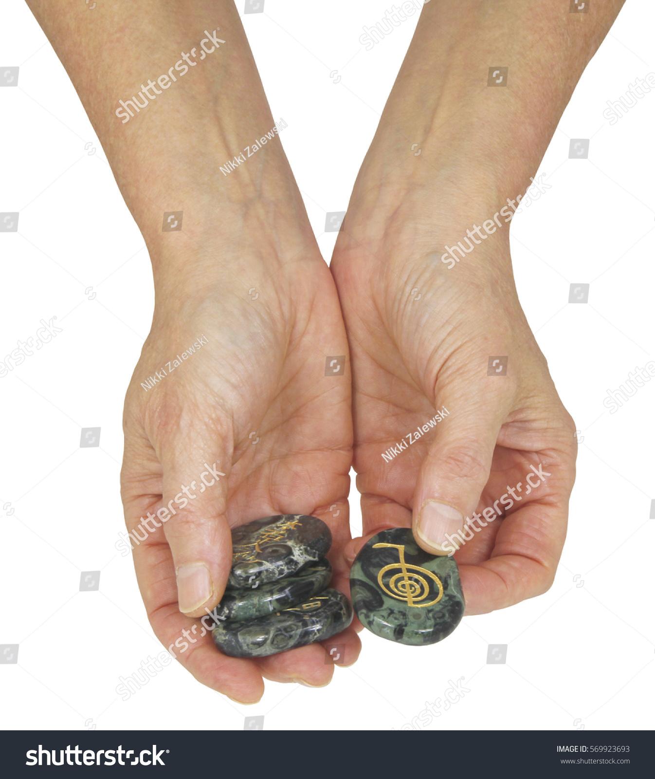 Choku rei reiki symbol female hands stock photo 569923693 the choku rei reiki symbol female hands holding a set of reiki chakra stones offering buycottarizona Images
