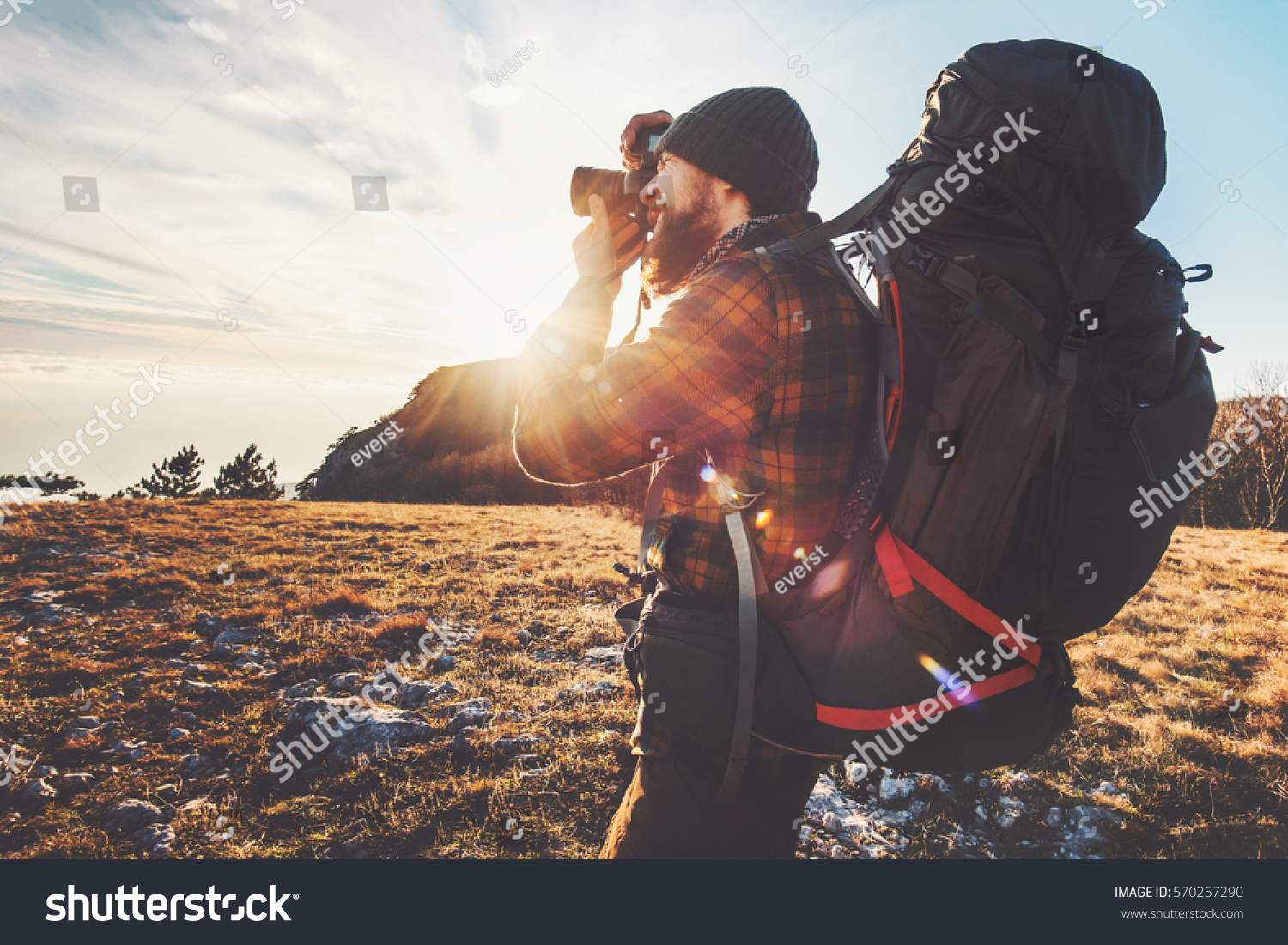 Man photographer with big backpack and camera taking photo of sunset mountains Travel Lifestyle hobby concept adventure active vacations outdoor  #570257290