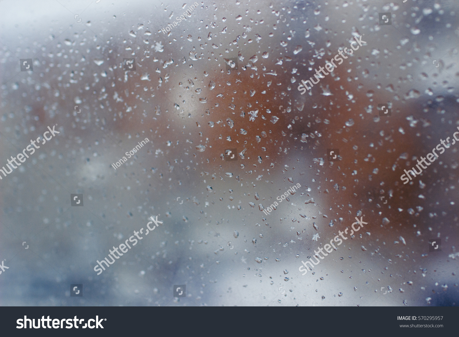 city landscape is hardly distinguishable through a muddy window with rain drops, orange structure #570295957
