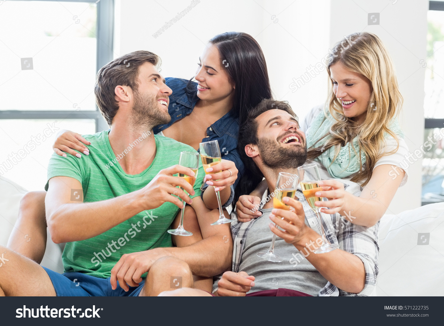 Smiling Friends Sitting On Sofa Drinking Stock Photo ...