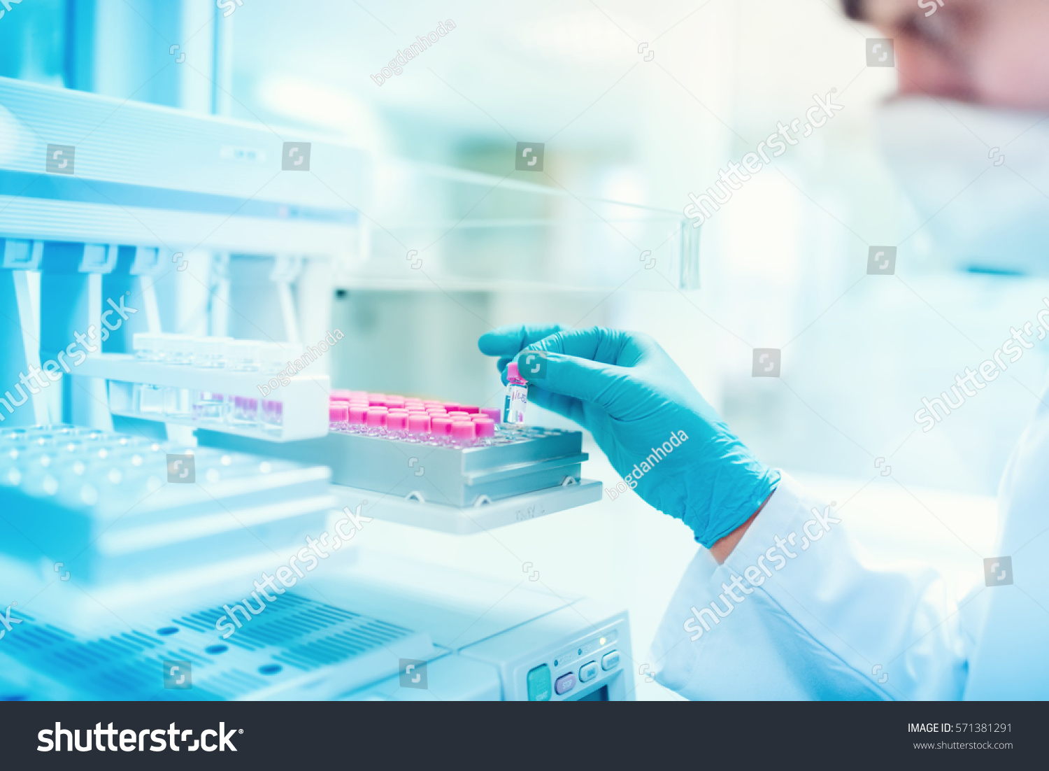 Close up of chemist scientist holding sample and examining test tube in special laboratory #571381291