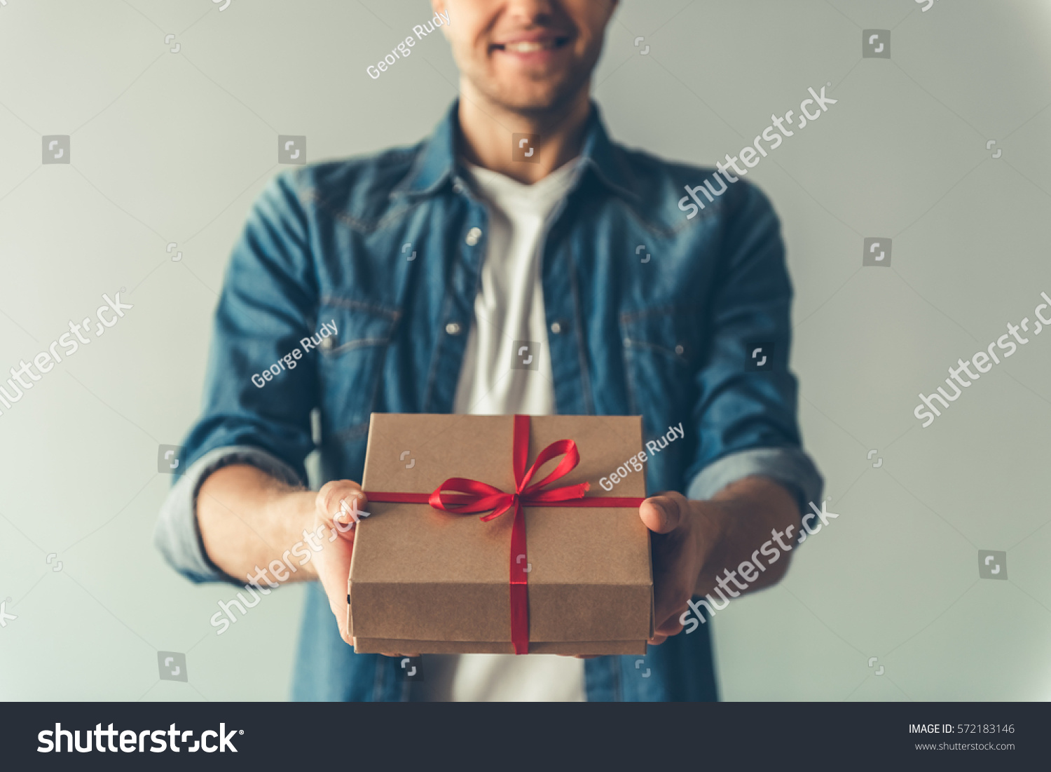 Cropped image of handsome romantic guy smiling while holding a present for his couple, on gray background #572183146