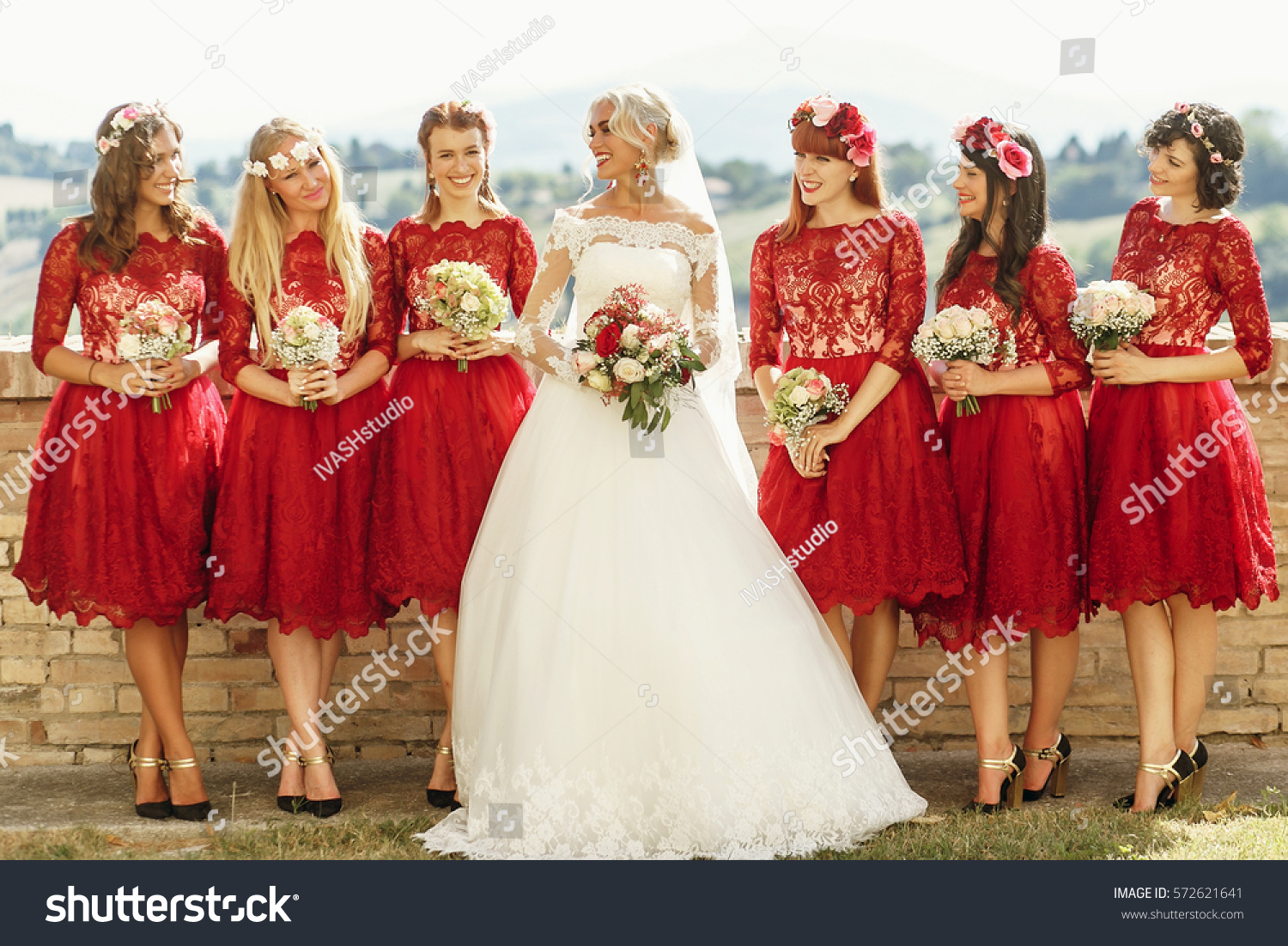 Stunning blonde bride bridesmaids short red stock photo 572621641 stunning blonde bride and bridesmaids in short red dresses pose before beautiful landscape ombrellifo Choice Image