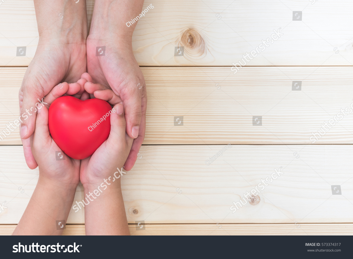 I love you Mom, Mother's Day celebration with parent woman holds young kid's hands supporting red heart, and charity donation for nursing and parenting children family health care concept  #573374317