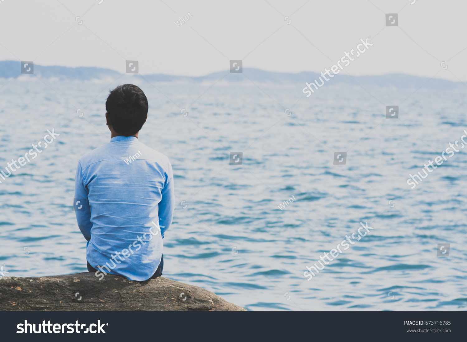 young wearing blue shirt sitting alone stock photo edit now