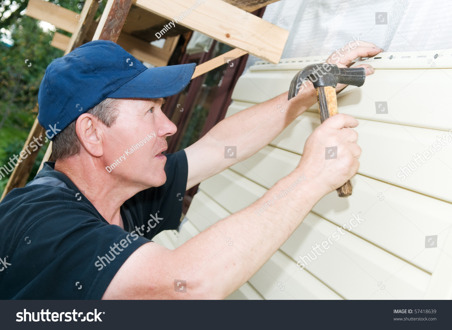 Worker Planking House With Plastic Siding Panels Stock
