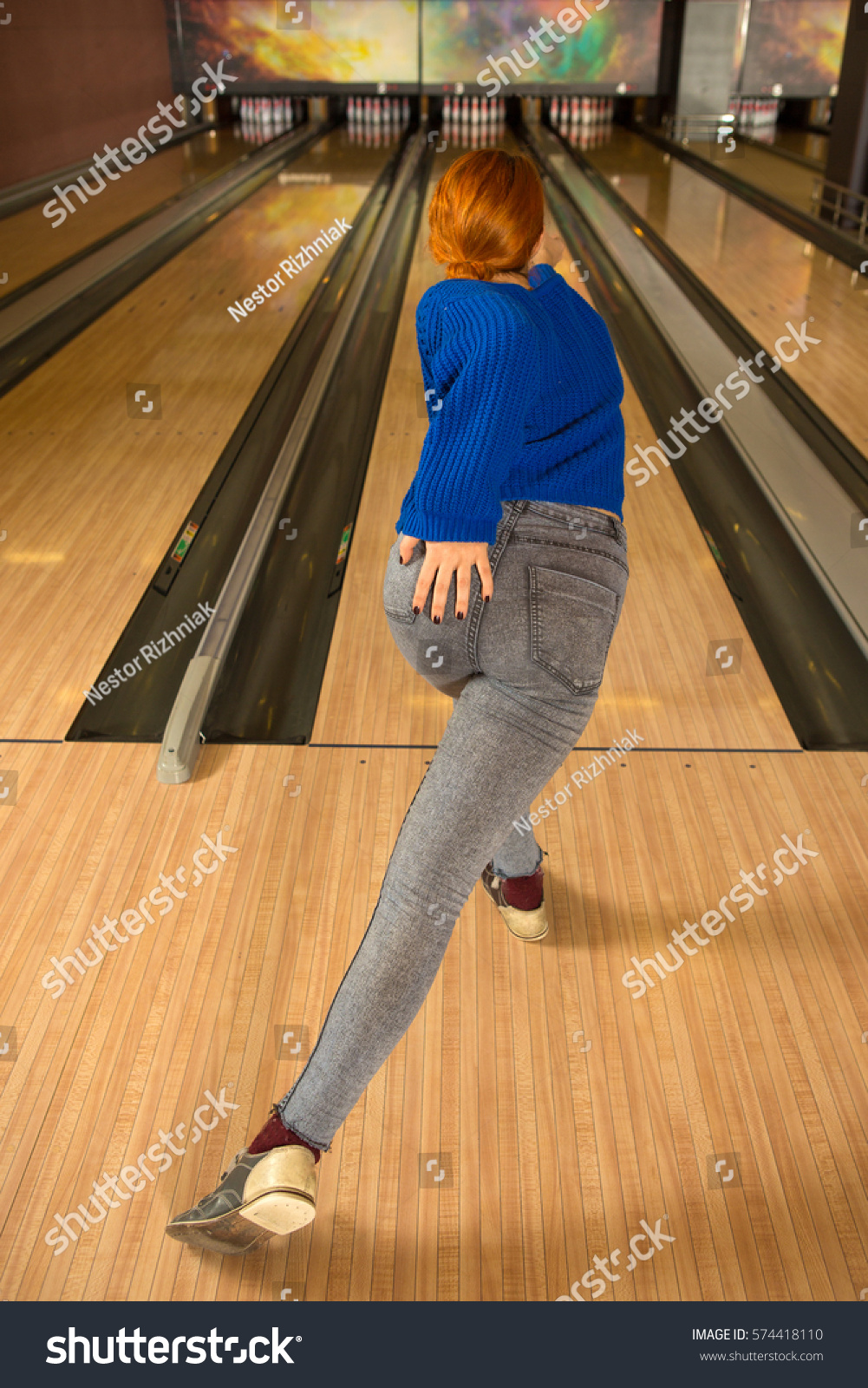 Vertical rearview shot of a woman playing bowling at the club feminine  seductive elegant body buttocks backside sexy player entertainment game  lifestyle ...