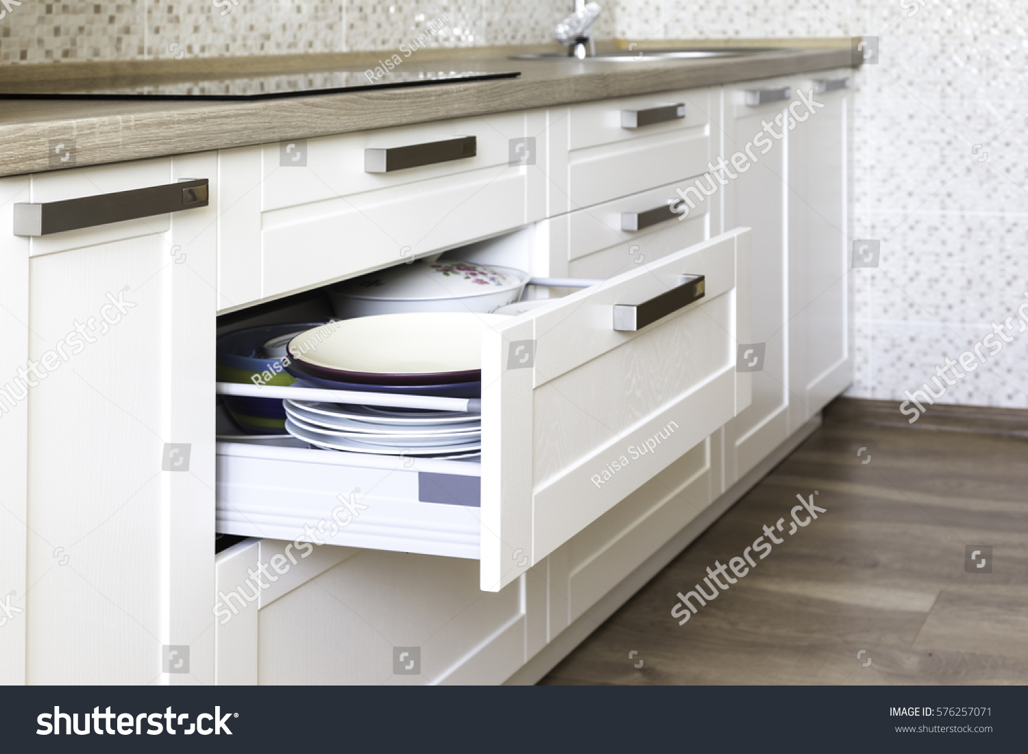 Opened kitchen drawer with plates inside, a smart solution for kitchen storage and organizing.  #576257071