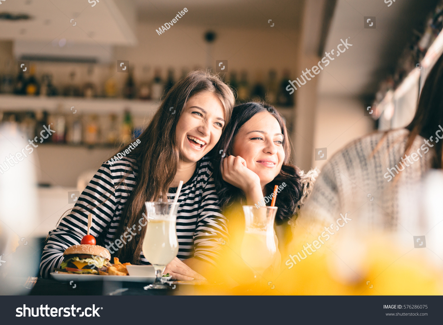 Old friends meeting up after long time for drinks and eating, talking about their memories. Girlfriends showing signs of affection, reliving beautiful moments from the past, being happy. #576286075