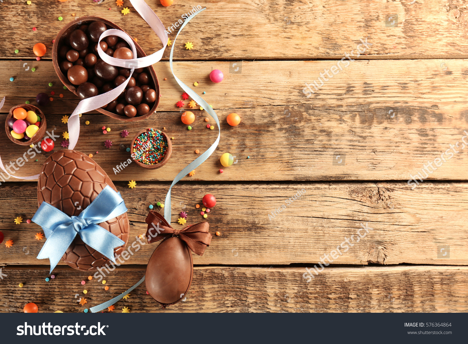 Chocolate Easter eggs with color ribbon bows on wooden background #576364864