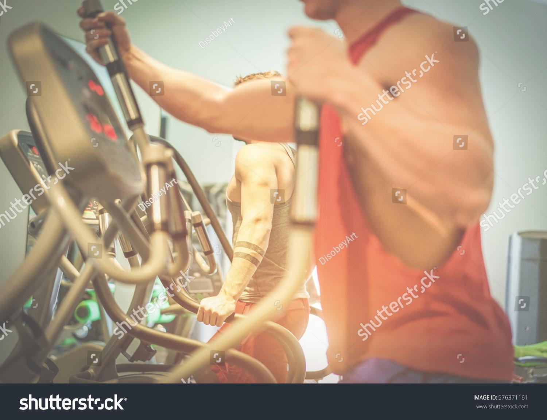 Fitness Men Using Eliptical Cross Trainer Stock Photo Edit Now