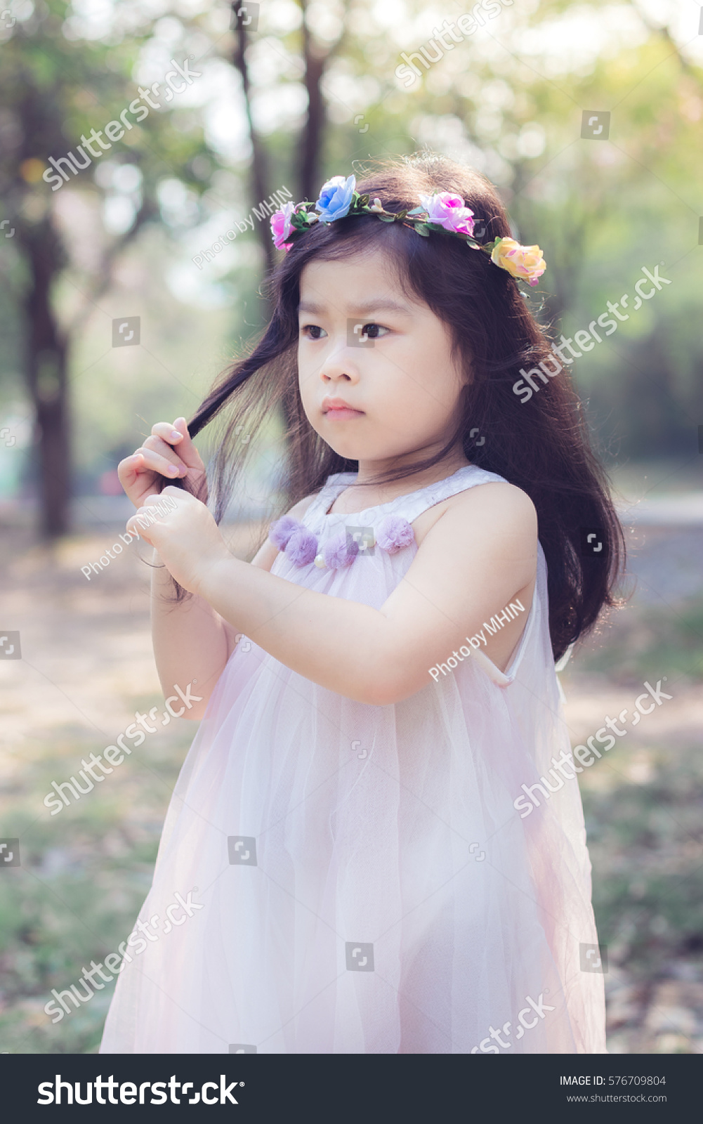 Asian little cute girl flower crown stock photo royalty free asian little cute girl with flower crown in the garden izmirmasajfo Gallery
