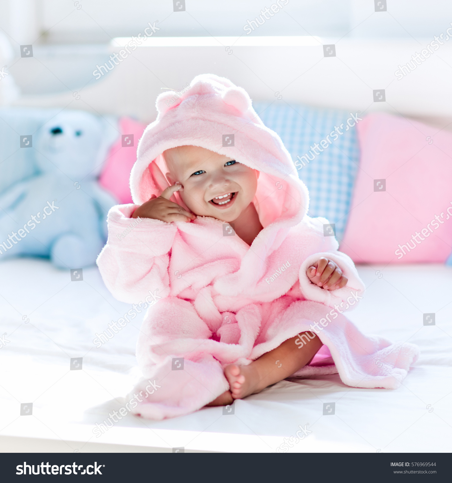 59387bff596 Cute happy laughing baby in soft bathrobe after bath playing on white bed  with blue and
