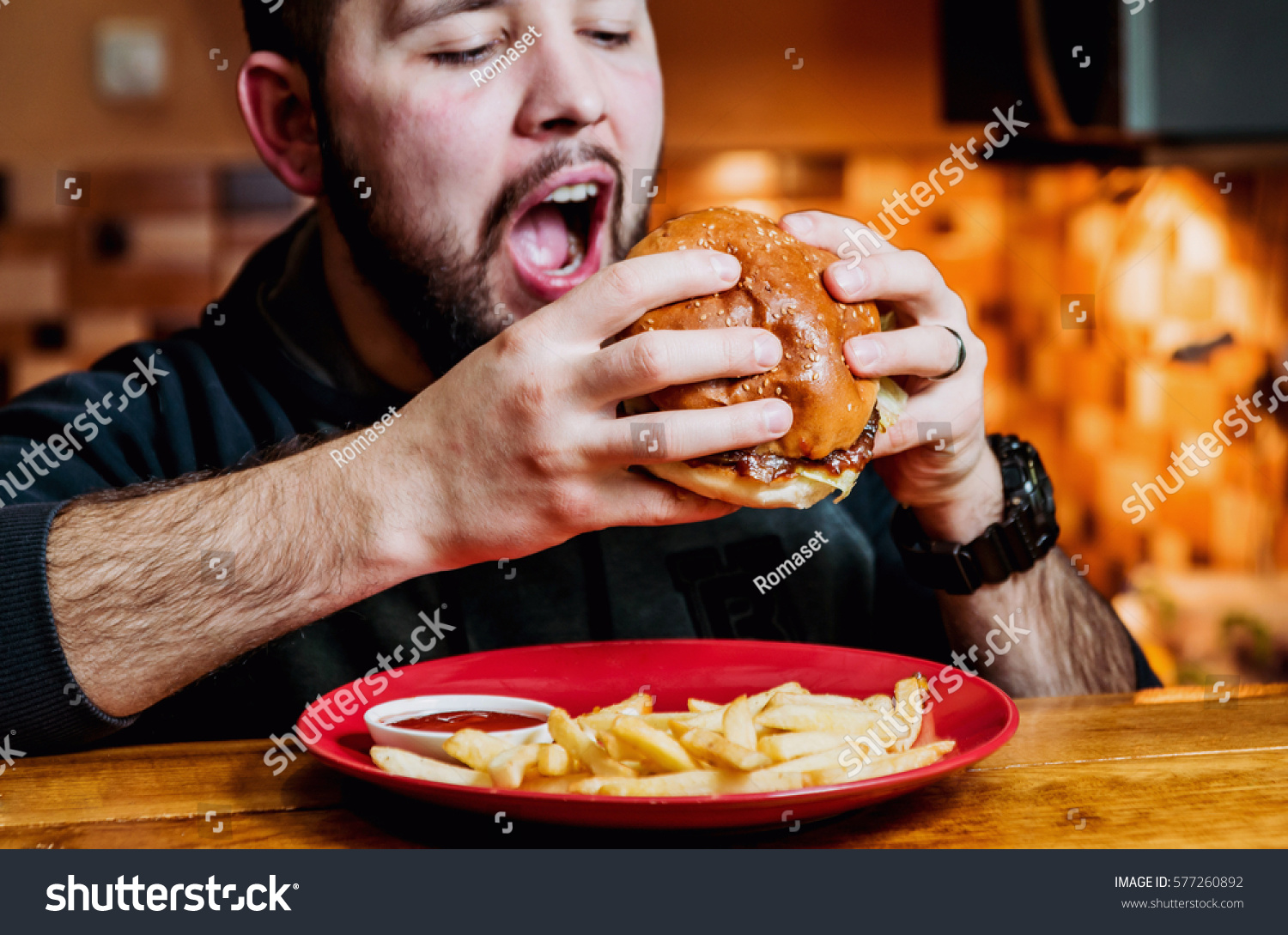 Young man eating a cheeseburger. Restaurant #577260892