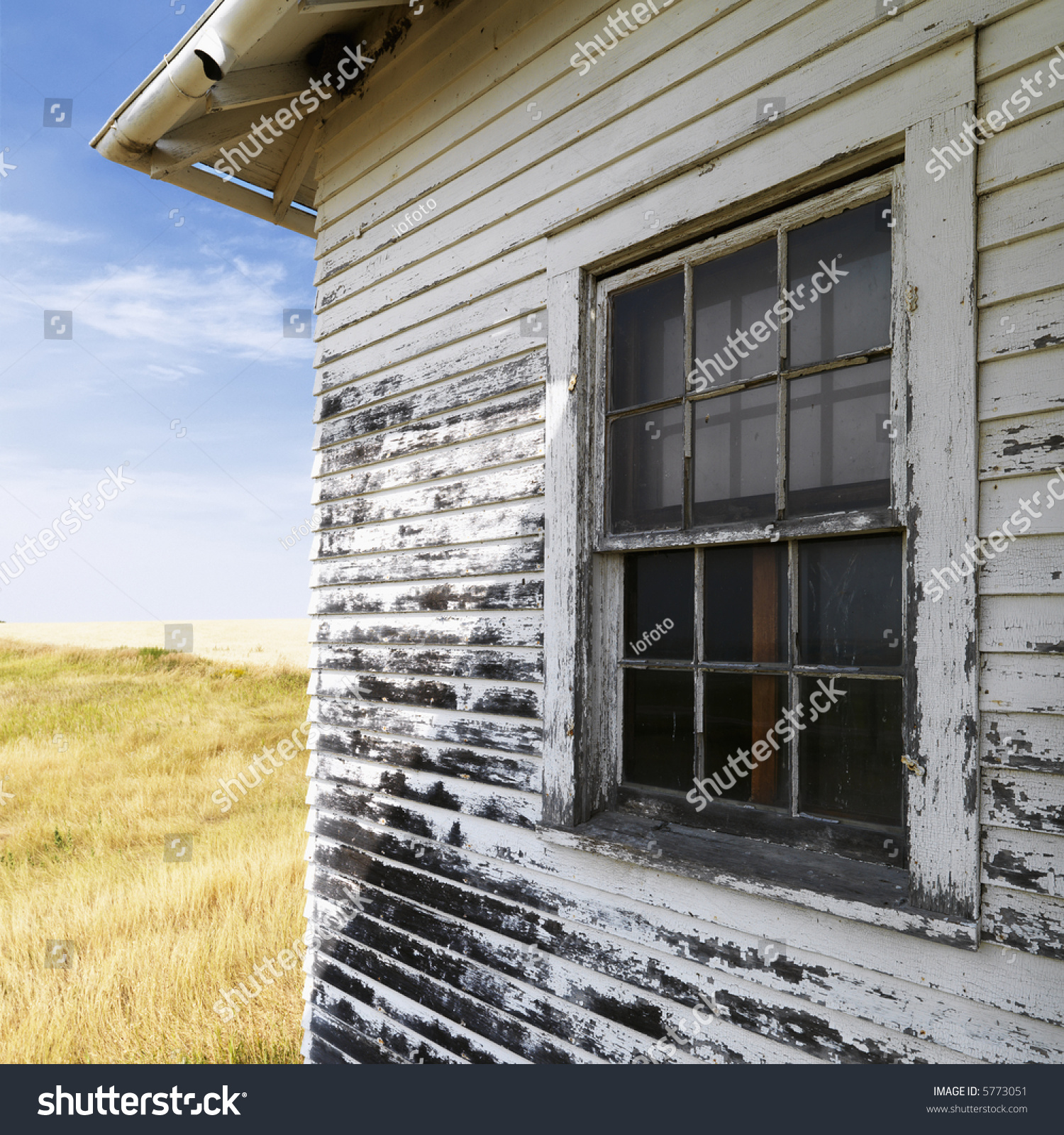 Exterior of weathered abandoned building with peeling paint and window in grassland stock photo - Exterior paint peeling concept ...