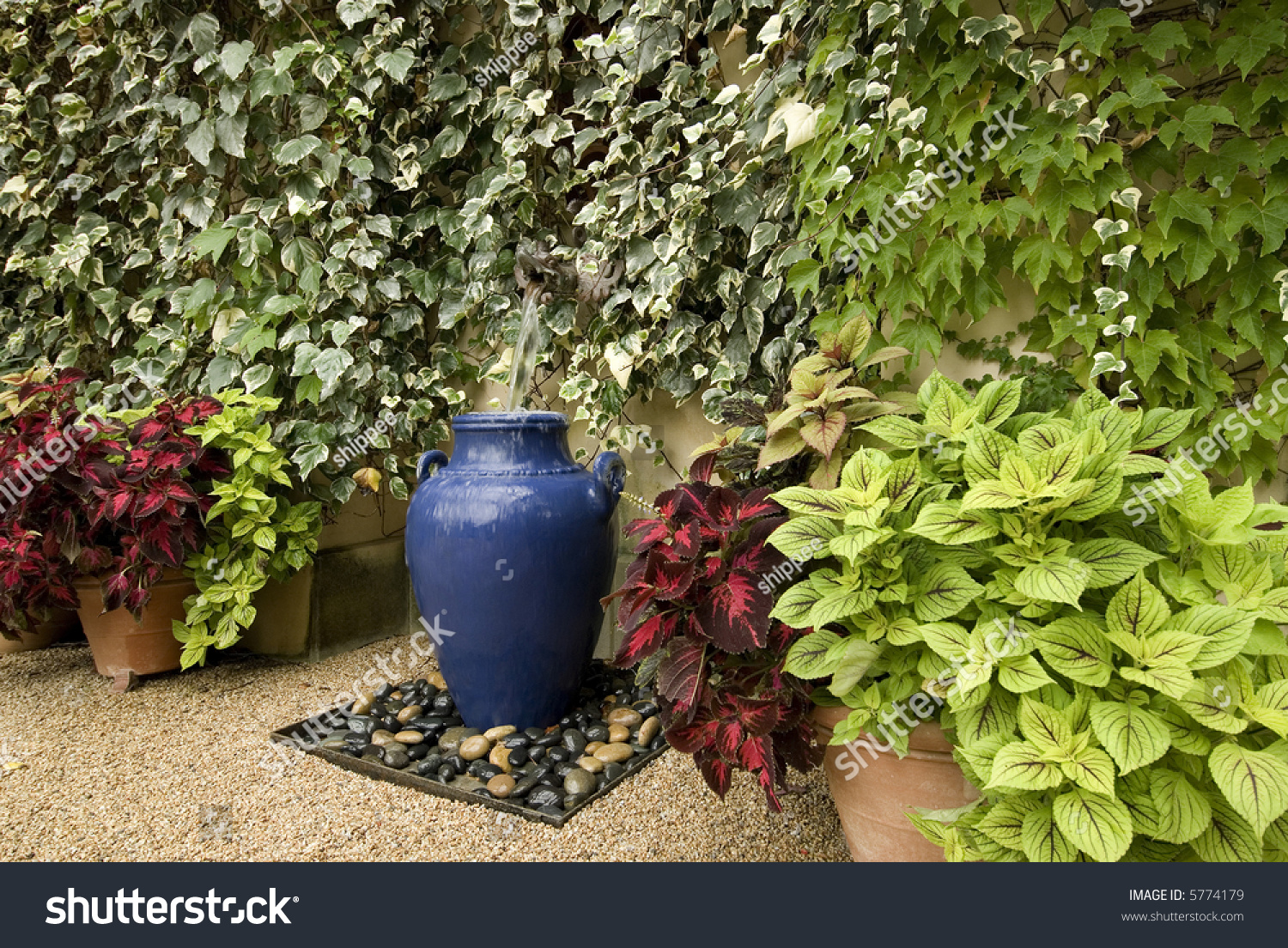 Garden Water Feature Using A Large Blue Pot Surrounded By Wall Of Ivy And Potted Plants Gravel