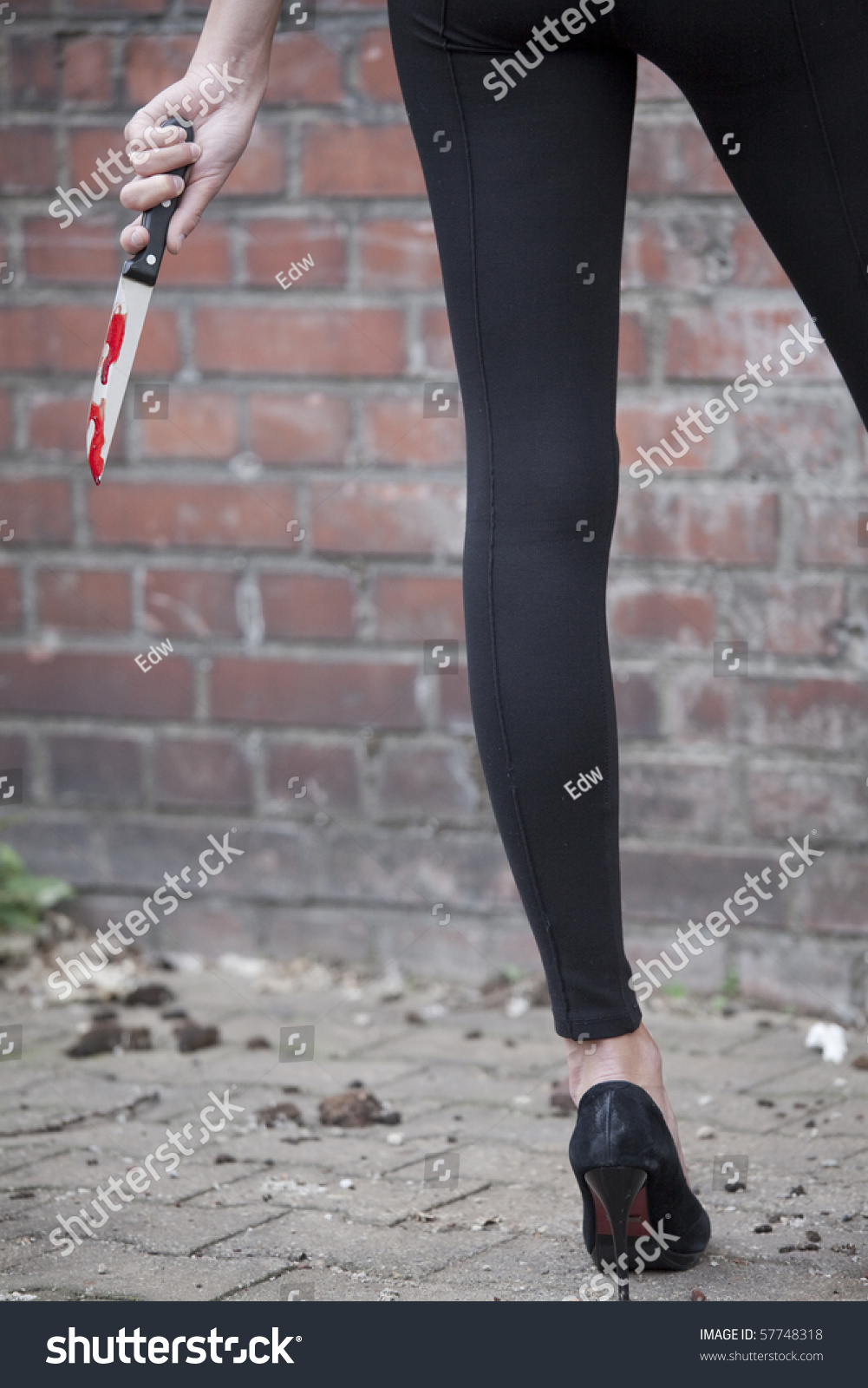 Young Woman Holding Bloody Knife Shot From Behind Stock