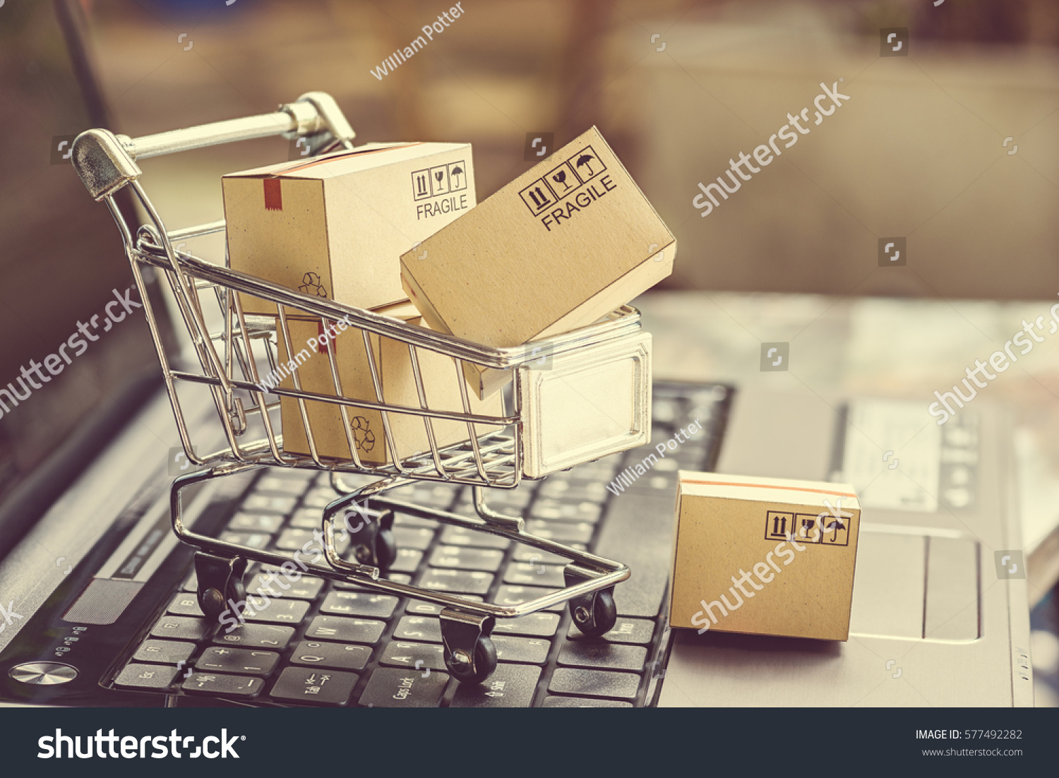 Paper boxes in a shopping cart on a laptop keyboard. Ideas about e-commerce, e-commerce or electronic commerce is a transaction of buying or selling goods or services online over the internet. #577492282