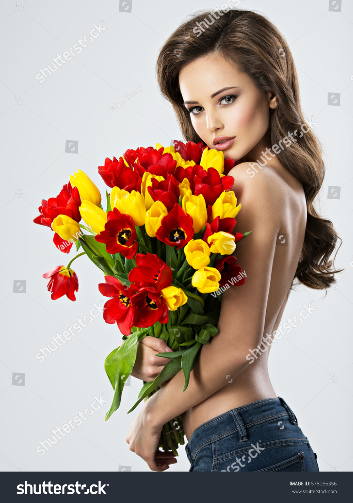 Nude Sexy young woman with flowers. Attractive model with bouquet of tulips