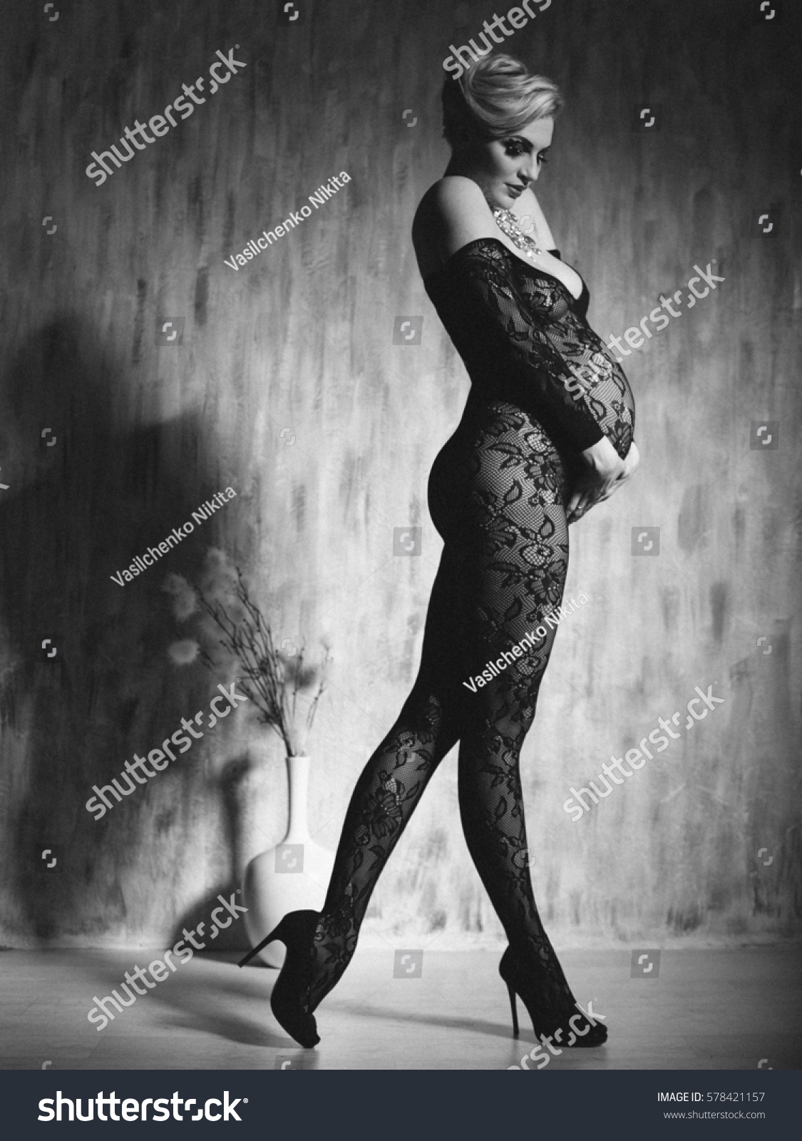 Pregnant woman in perfect form. Model in the dark. Sexy pregnancy. - Image