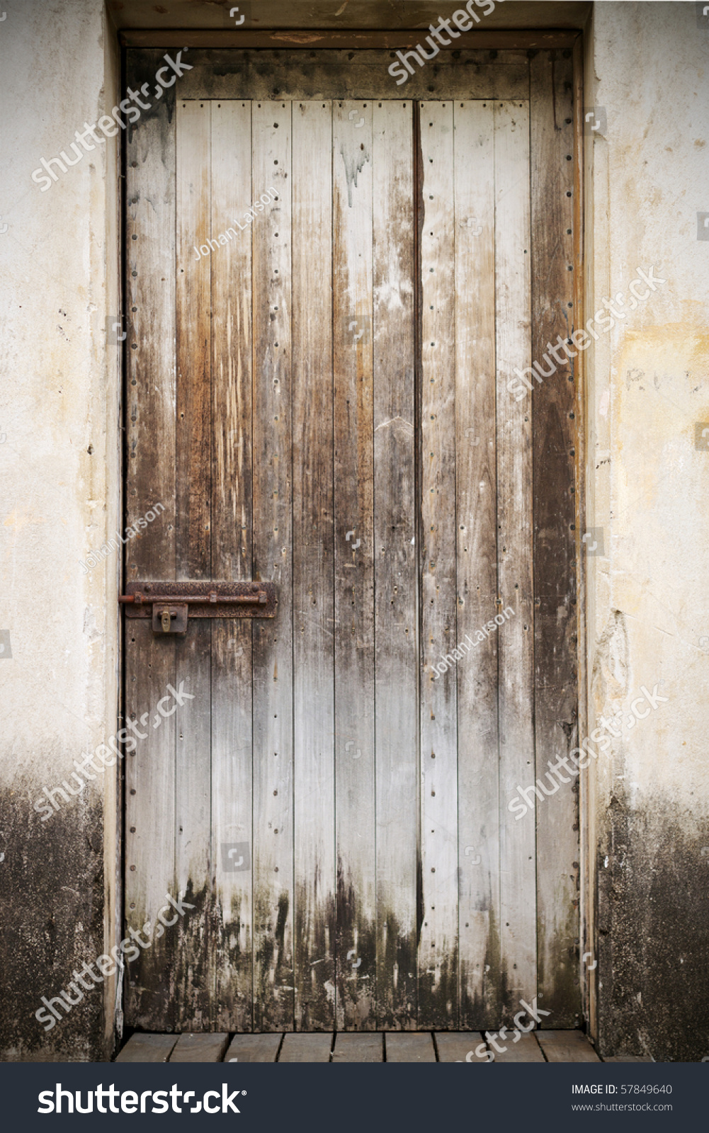 An Old Closed Rustic Wooden Front Door With A Rusty Lock