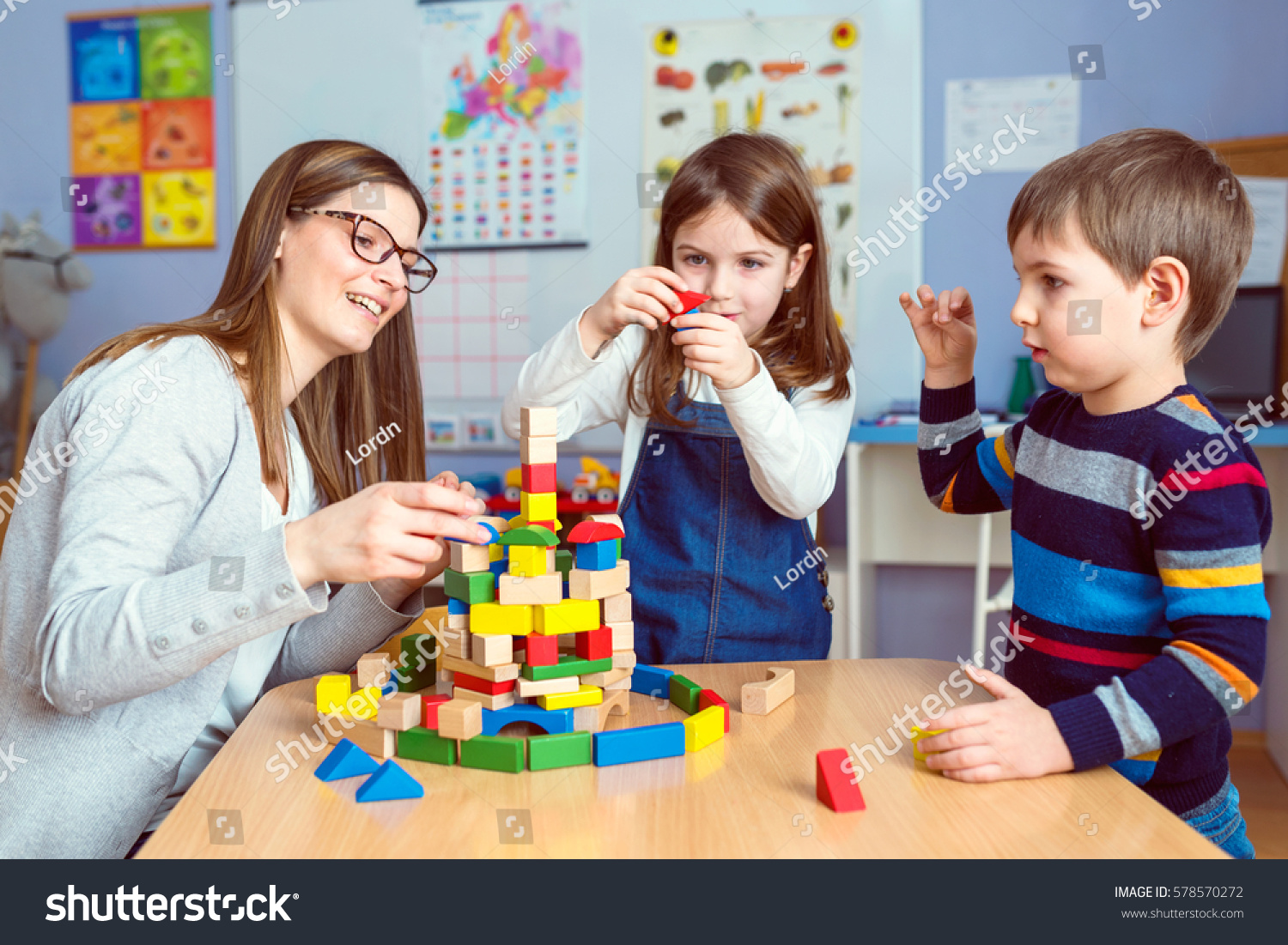 Kinder Garden: Teacher Kids Playing Together Colorful Toy Stock Photo