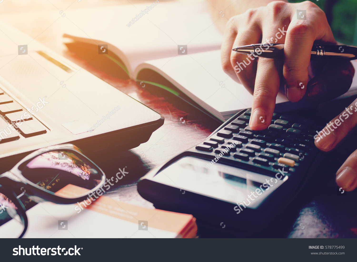 Close up woman doing finance at home office with calculate expenses #578775499