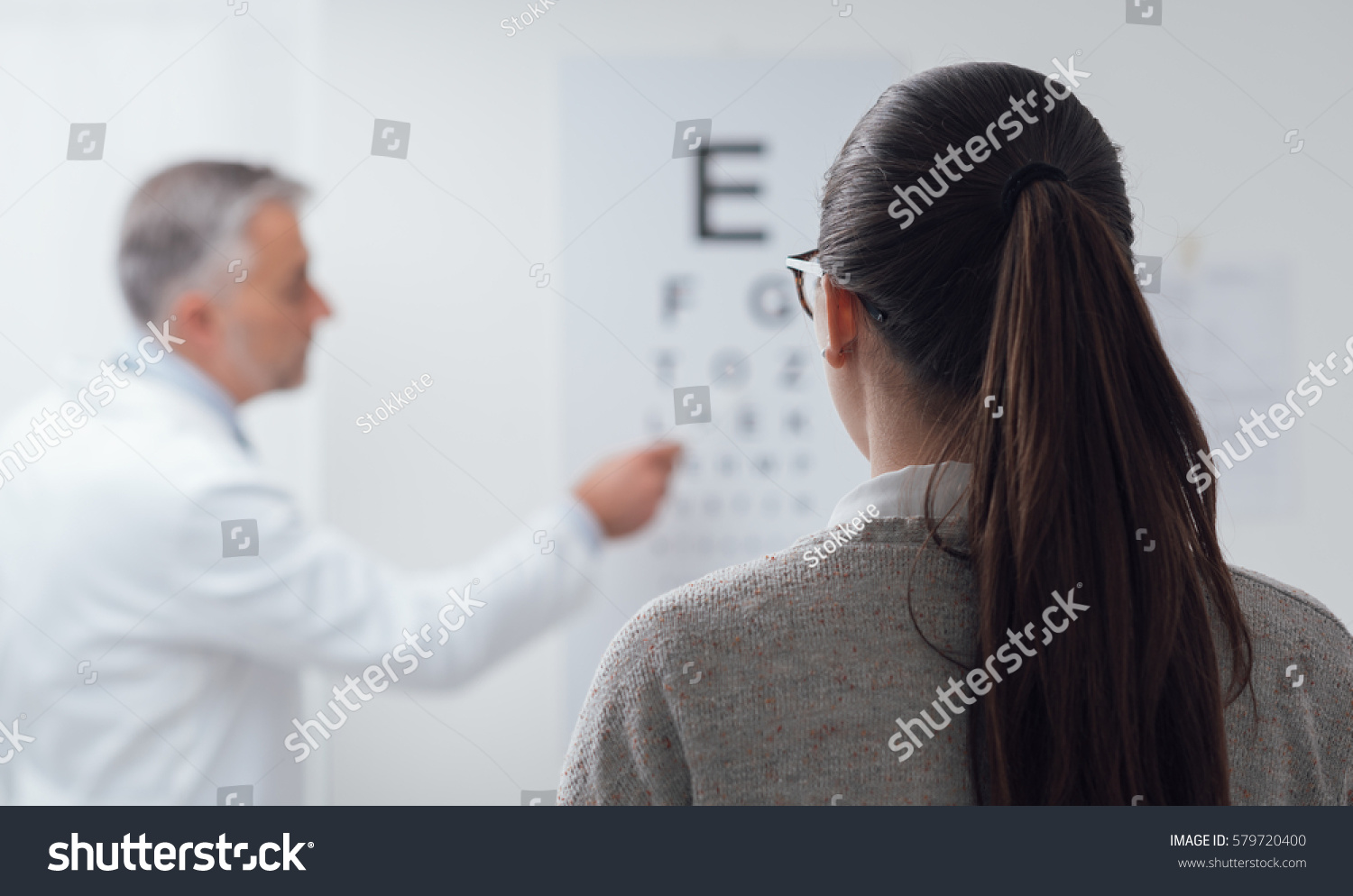 Woman Reading Eye Chart Ophthalmologist Pointing Stock Photo