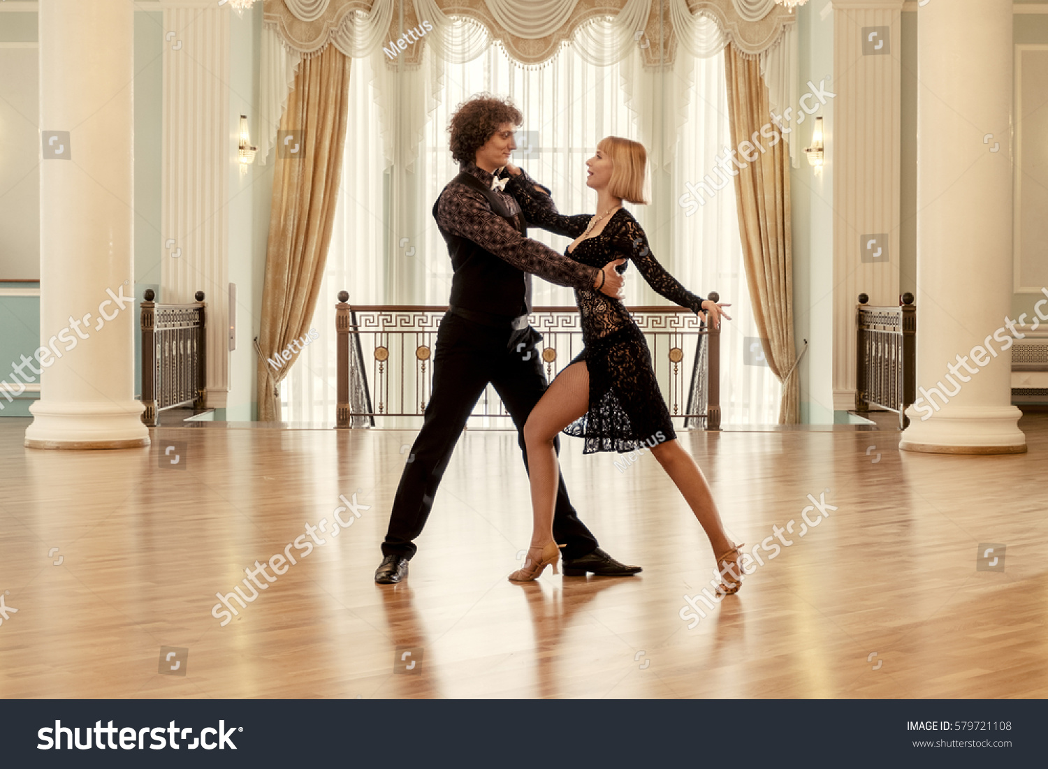 Loving couple dancing latino dance in rich dance-hall toned image