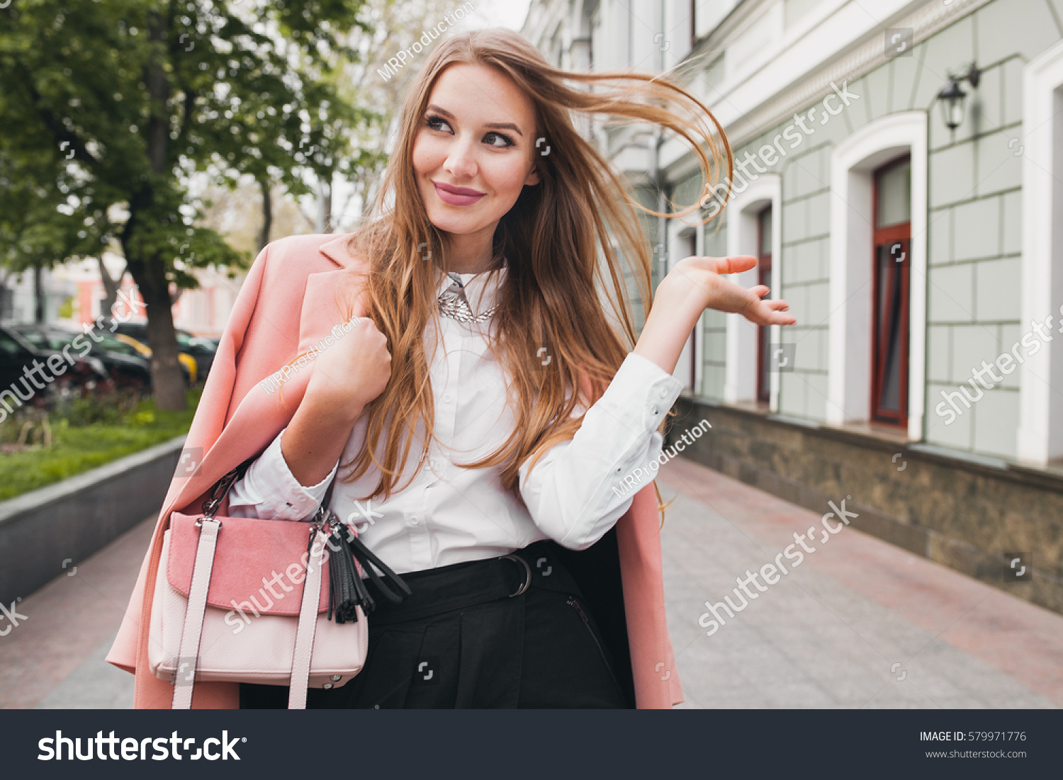 young beautiful stylish woman walking in pink coat, holding purse in hands, smiling, happy, street style, spring summer trend, black skirt, white shirt, flirty #579971776