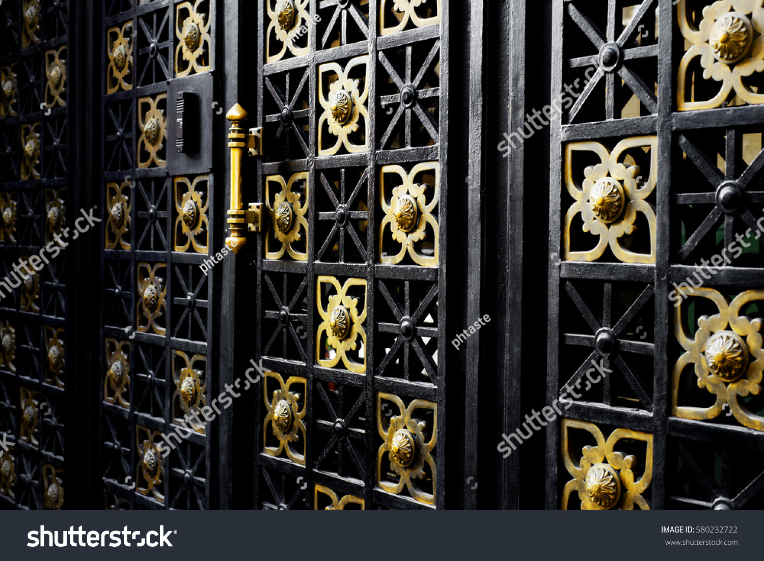 Old black iron gate golden ornaments stock photo