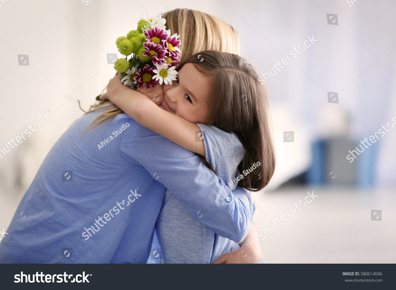 Cute little girl greeting her mother at home. Mother's day concept #580614046