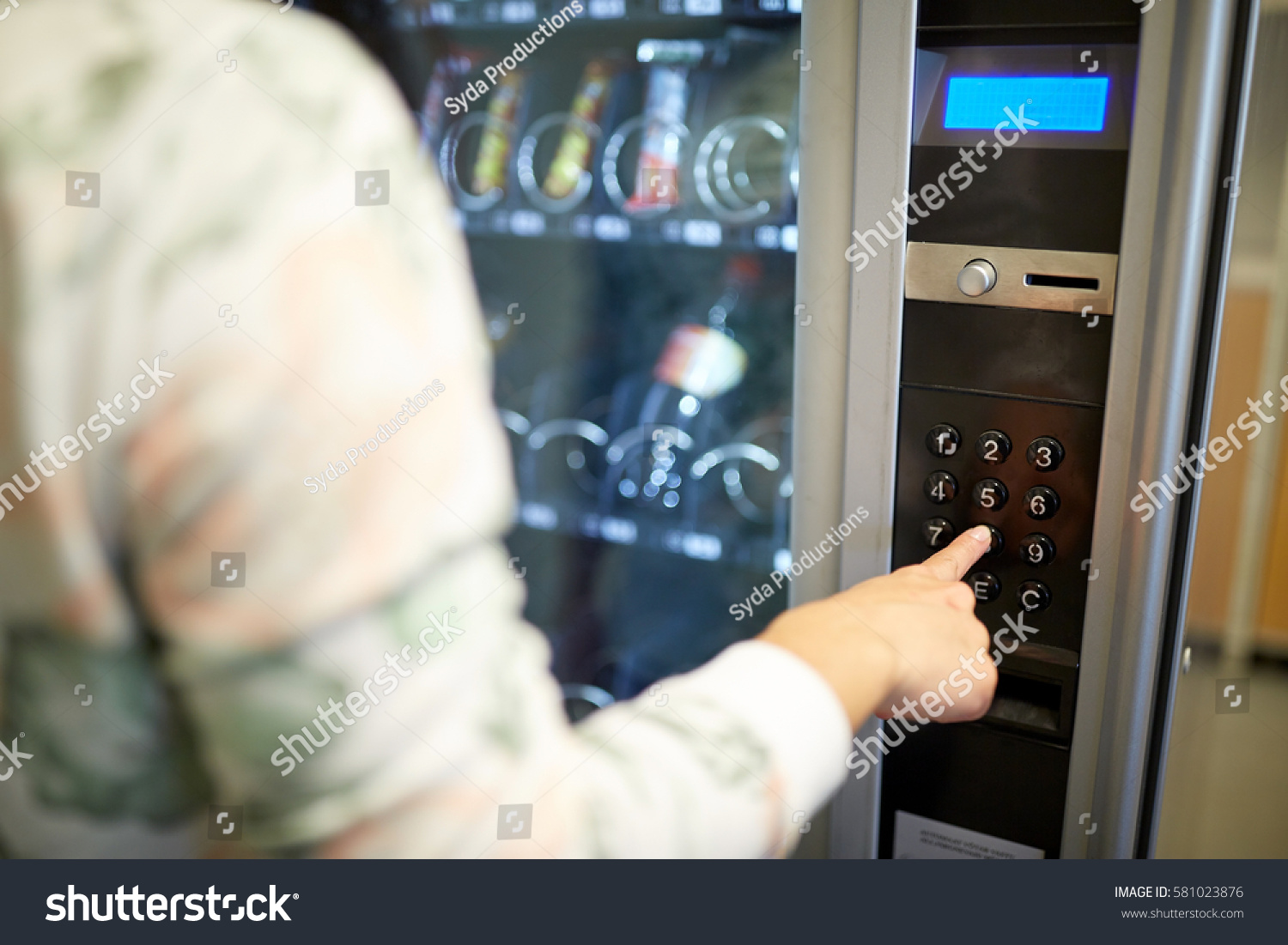 sell, technology and consumption concept - hand pushing button on vending machine operation panel keyboard #581023876