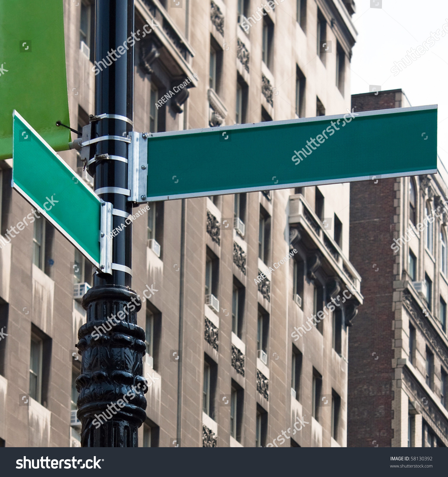 two blank green street signs on a post at the intersection