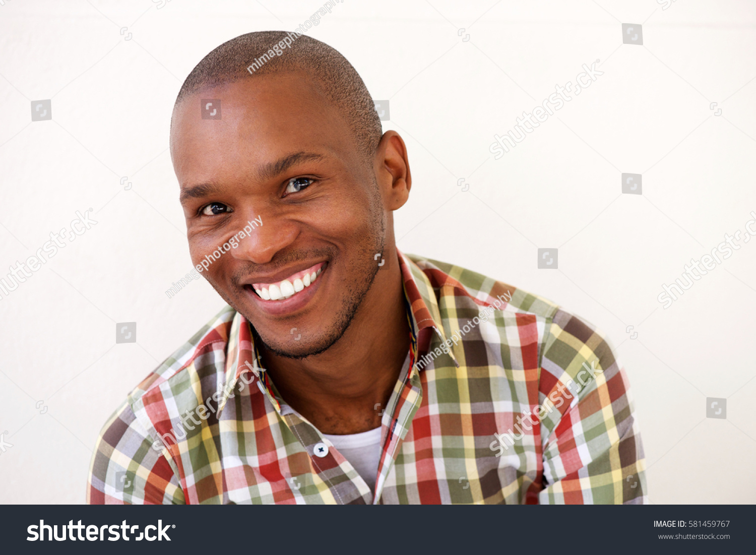 974df57fd06 Close up portrait of cheerful young black man smiling against white  background