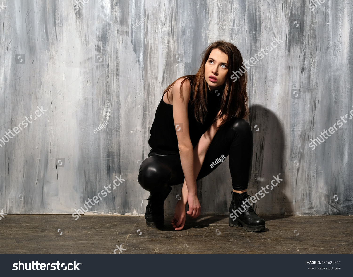 Young girl in black open T-shirt and leather leggings. Long-haired woman posing on gray backdrop. Sitting pose: shoulders open, hands hang between legs, patent leather shoes. #581621851