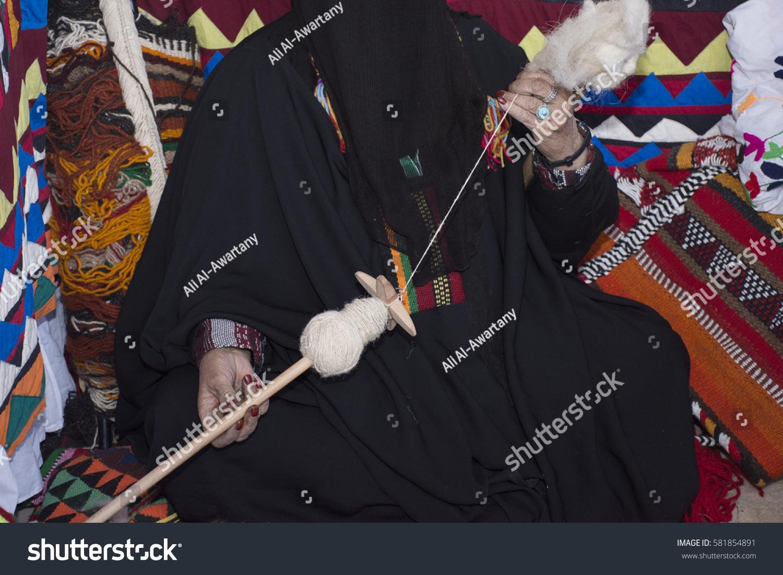 stock-photo-saudi-woman-weaving-wool-tra