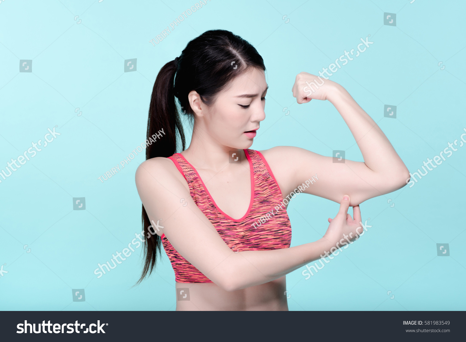 2b147b78a2151 Asian woman checking arm cellulite after workout. Beauty face and natural  makeup sports bra outfit