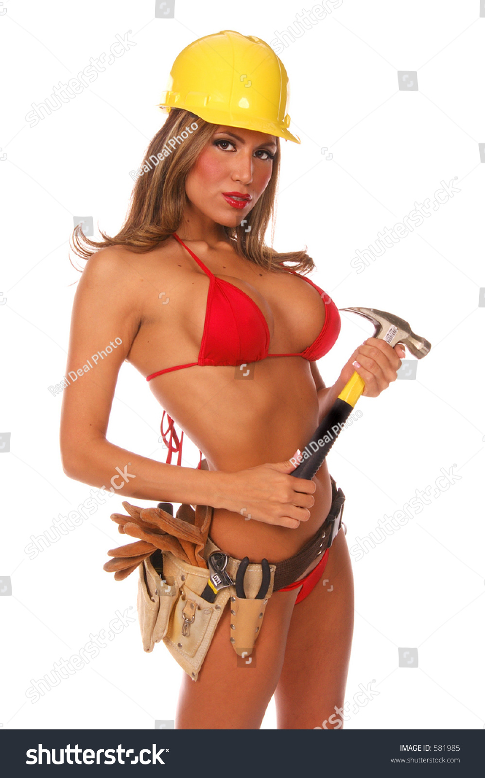 Sexy latino female construction worker in bikini, hardhat and tool belt with a hammer in her hands #581985