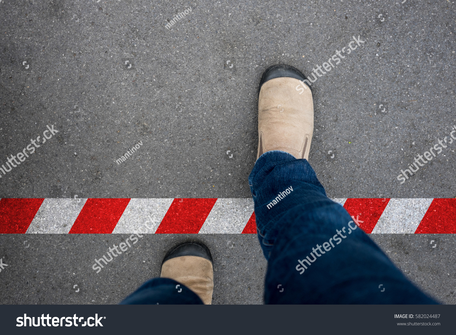 One walking across red and white line to prohibited area. Breaking the rule beyond the limit. #582024487