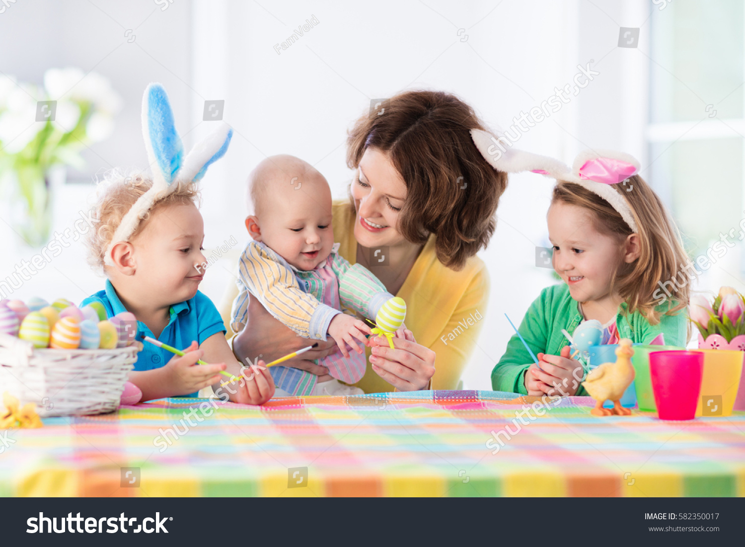 mother and children painting colorful eggs mom toddler preschooler and baby with bunny - Children Painting Images