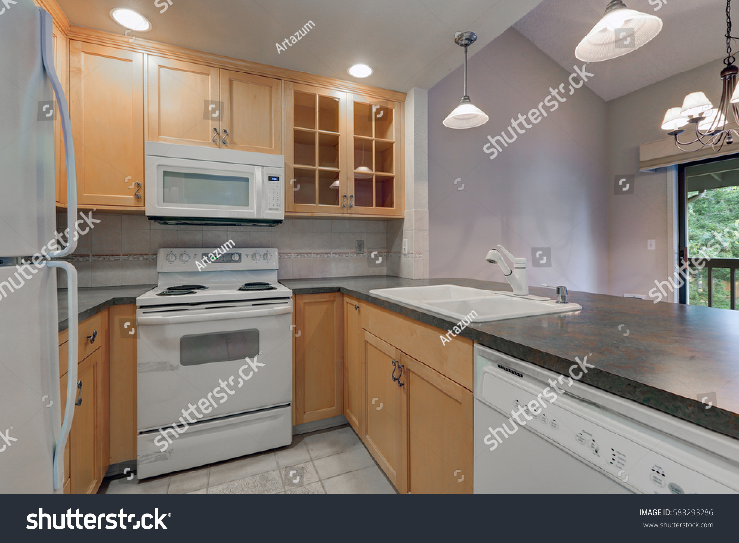 Tidy compact kitchen with maple cabinets dark grey counters white appliances and beige tile & Tidy Compact Kitchen Maple Cabinets Dark Stock Photo (Edit Now ...