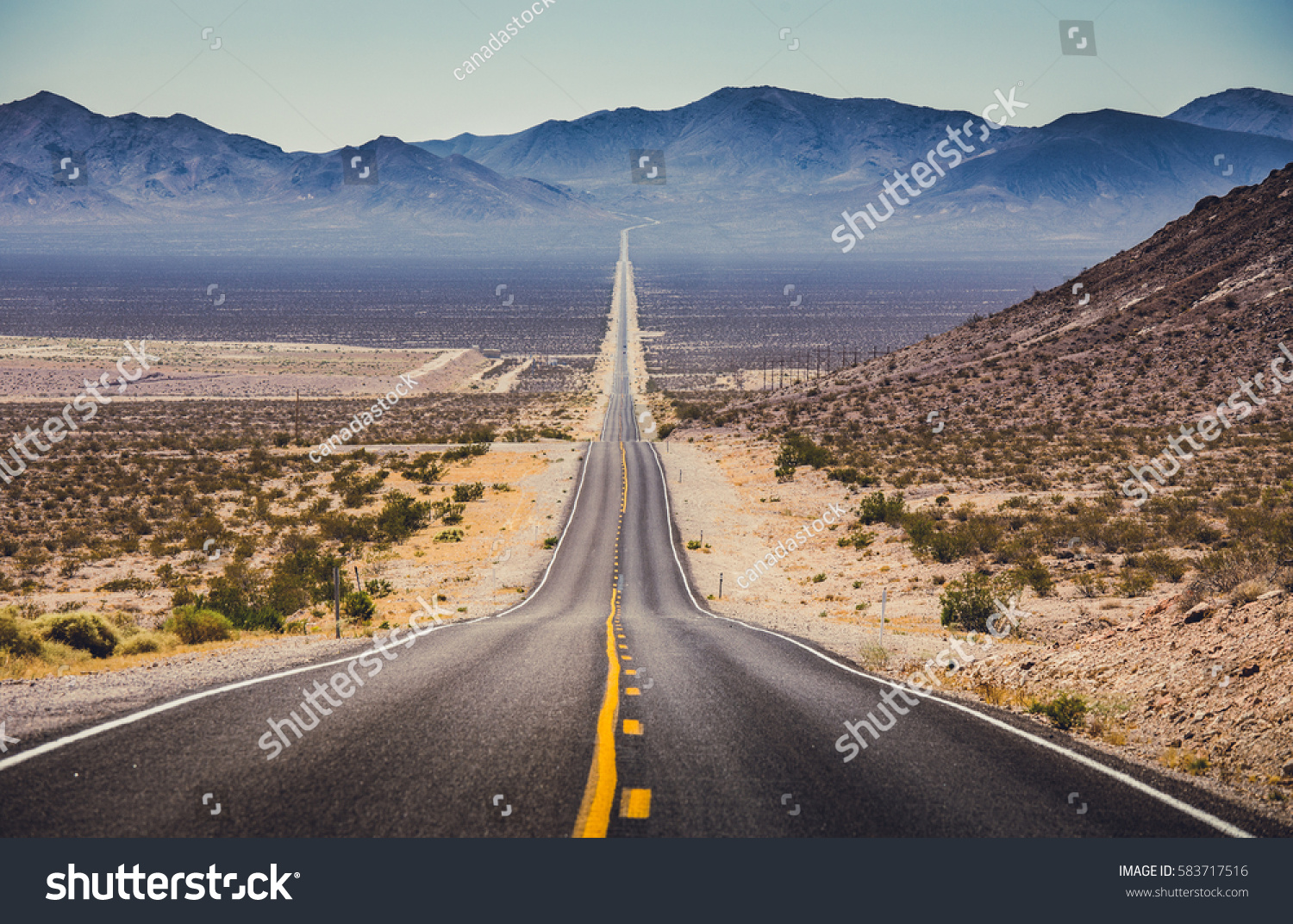 Classic panorama view of an endless straight road running through the barren scenery of the American Southwest with extreme heat haze on a beautiful hot sunny day with blue sky in summer #583717516