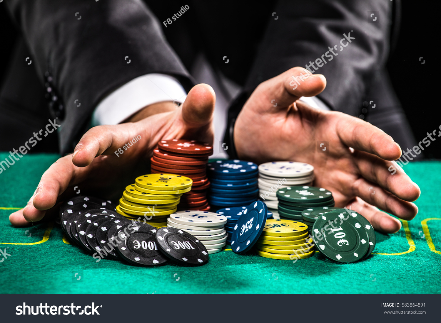 casino, gambling, poker, people and entertainment concept - close up of poker player with chips at green casino table #583864891