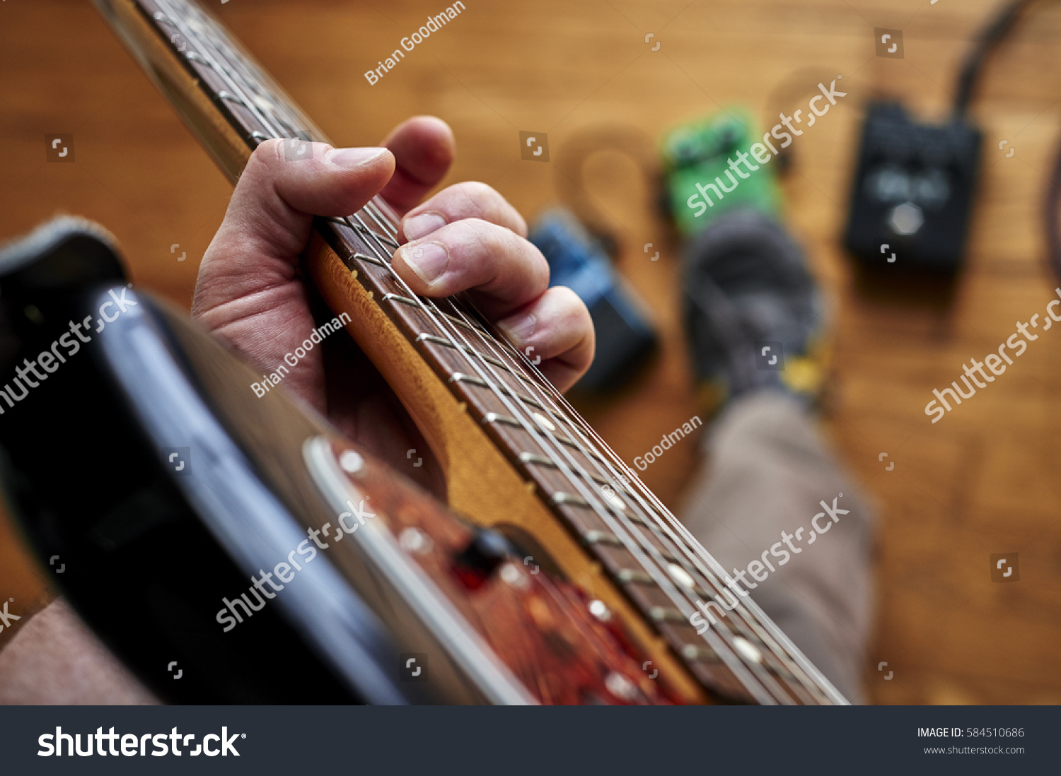 Person Playing Guitar Using Effect Pedals Stock Photo