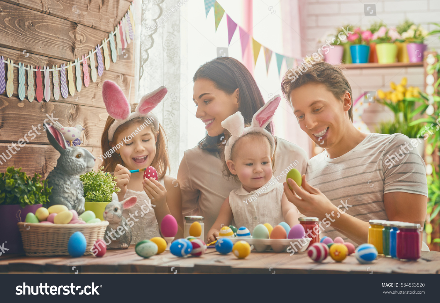 Mother, father and daughters are painting eggs. Happy family are preparing for Easter. Cute little child girl wearing bunny ears. #584553520