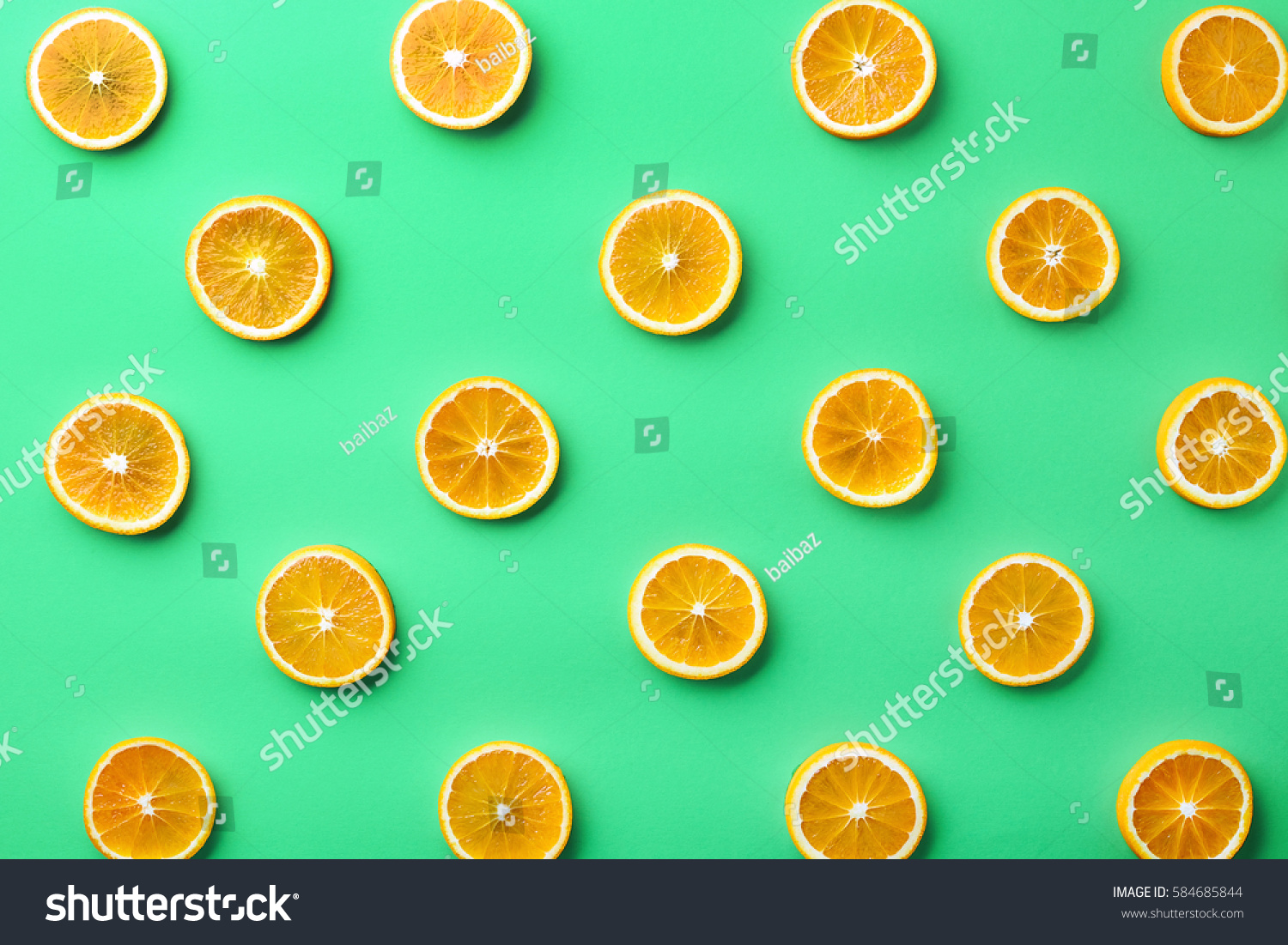 Colorful fruit pattern of fresh orange slices on green background. From top view