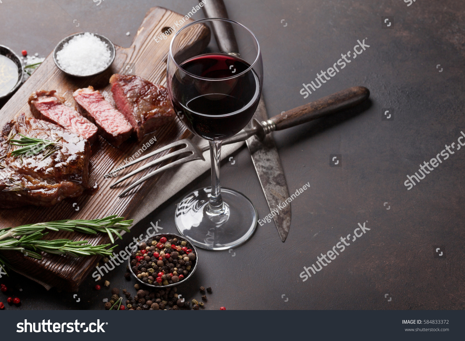 Grilled ribeye beef steak with red wine, herbs and spices on stone table #584833372
