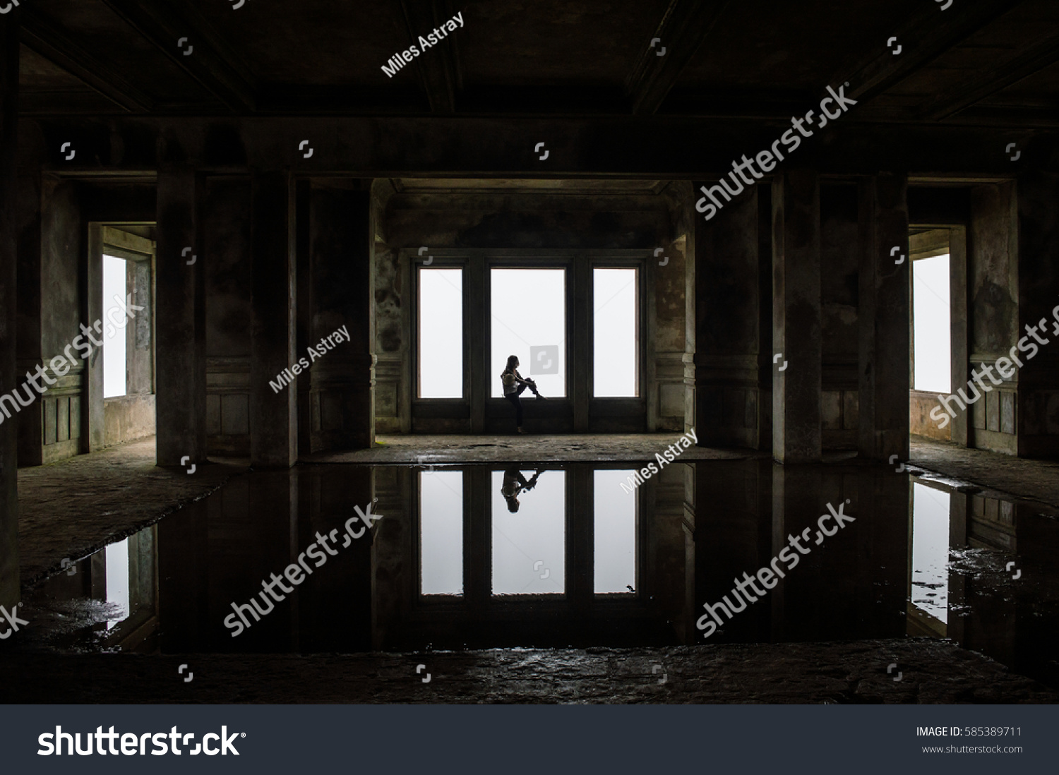Woman Sitting On A Windowsill Inside The Abandoned Casino At Bokor Hill  Station In Cambodia