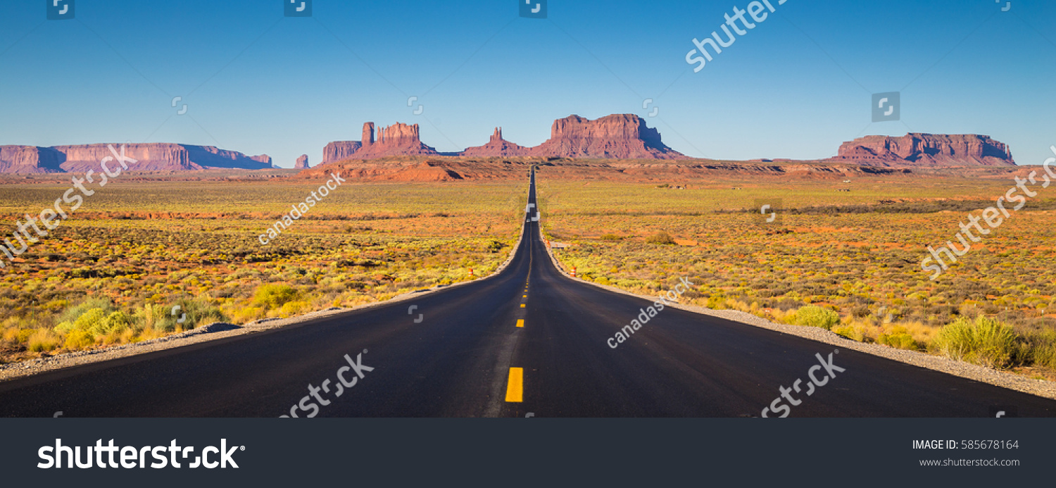 Classic panorama view of historic U.S. Route 163 running through famous Monument Valley in beautiful golden evening light at sunset on a beautiful sunny day with blue sky in summer, Utah, USA #585678164
